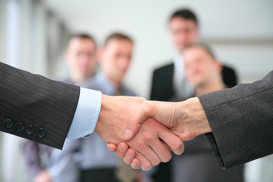 Corporate-Handshake-with-business-people-in-the-background1